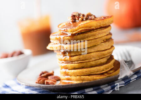 Tasty pumpkin pancakes with caramel sauce and nuts. Selective focus. Autumn comfort food, american Thanksgiving day breakfast - Stock Photo