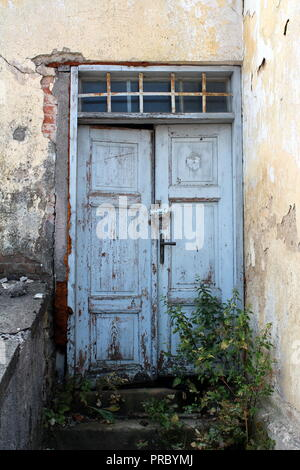 Light blue old dilapidated wooden doors locked with small padlock with windows above secured with rusted metal bars on abandoned house with stone step - Stock Photo
