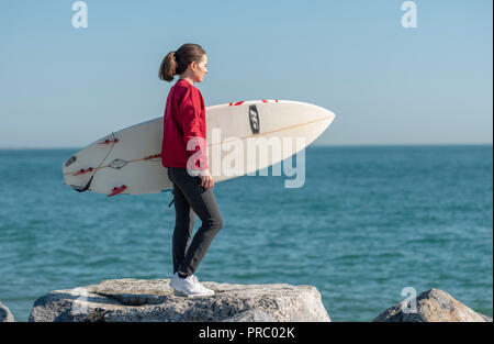 woman standing on rocks holding a surfboard checking out the sea before surfing. - Stock Photo