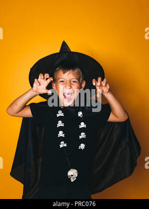 boy is dressed as a halloween witcher in front of orange background - Stock Photo