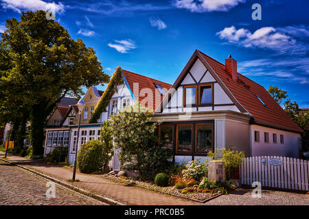 Row of small houses on a cobblestone street as seen in this tourist town - Stock Photo