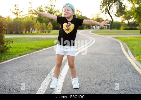 Fashion kid concept - portrait of stylish little cute girl child wearing a cap outdoors in the city.