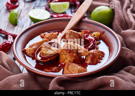 Carne Adobada or hearty Red Chile and Pork Stew in a clay bowl with spoon on an old wooden table with lime slices and dried chile, mexican cuisine, ho - Stock Photo