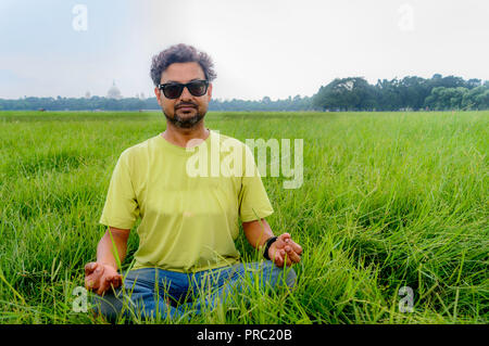Yoga at park. Senior bearded man in lotus pose sitting on green grass. Concept of calm and meditation.Young man in sunglasses meditating outdoors in t - Stock Photo