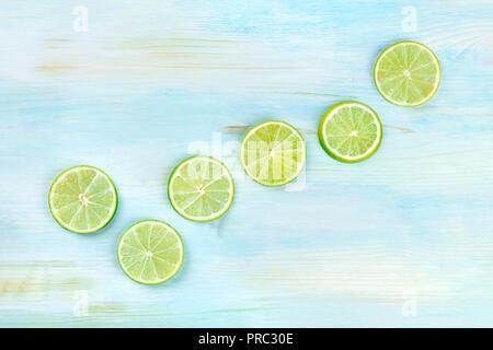 An overhead photo of many vibrant lime slices on a teal blue background - Stock Photo