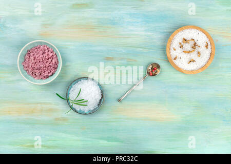 Gourmet spices. An overhead photo of various types of salt and pepper with different addings, shot from above on a teal blue background with copy space - Stock Photo