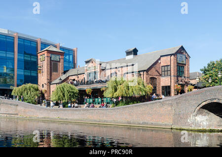 People drinking outside the Malt House pub next to the canal in Brindley Place, Birmingham - Stock Photo