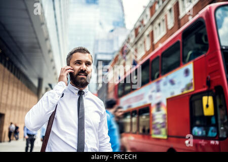 Hipster businessman on the street in London, making a phone call. - Stock Photo