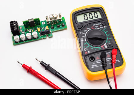 Electric multimeter with red and black probe, display indicating zero, with printed circuit board. Isolated on a white background with a clipping path - Stock Photo