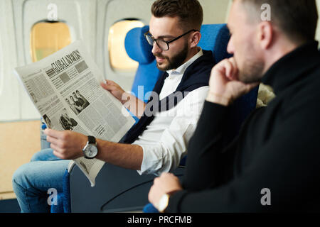Business People Reading Newspaper in Plane - Stock Photo