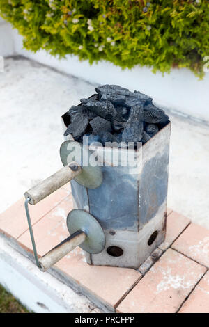 Smoking charcoal chimney starter bucket for barbecue in a backyard garden - Stock Photo
