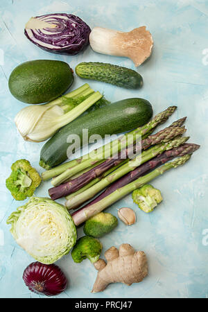 Set collection spring summer seasonal vegetables asparagus zucchini cabbage etc over on blue background. Flat lay. Overhead. - Stock Photo