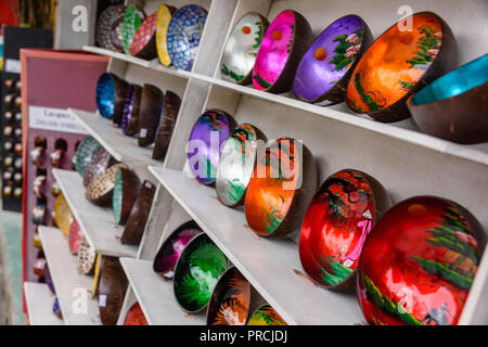 Decorated bowls made from coconut shells on sale at a souvenir shop. - Stock Photo