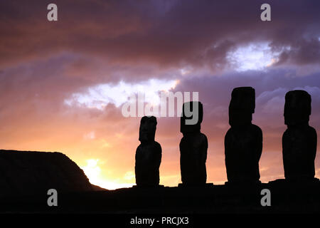 Stunning Purple Sunrise Cloudy Sky over the Silhouette of the Giant Moai statues of Ahu Tongariki Archaeological Site, Easter Island, Chile - Stock Photo