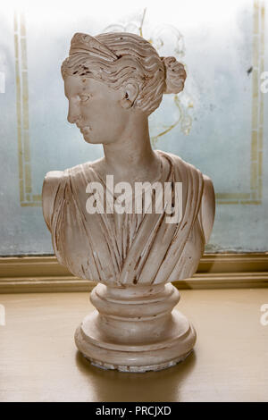 Italian marble bust the goddess Tyche by Umberto Frilli, with her head turned and wearing her distinctive tiara on the window sill of a stately hou - Stock Photo