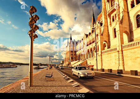 View of Buda and river Danube with boats from the embankment near the Hungarian Parliament at sunset. - Stock Photo