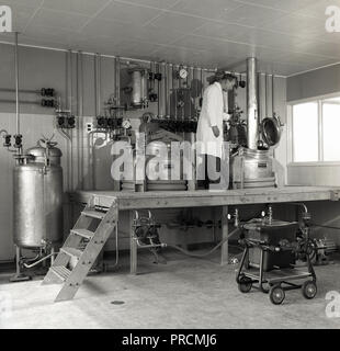 1950s, historical, a white-coated malet echnician working with steel pressure tanks, while standing on a raised platform, England, UK. - Stock Photo
