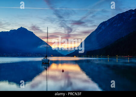 A sailboat in front of a colorful sunrise at the Lake Achensee in Austria. - Stock Photo