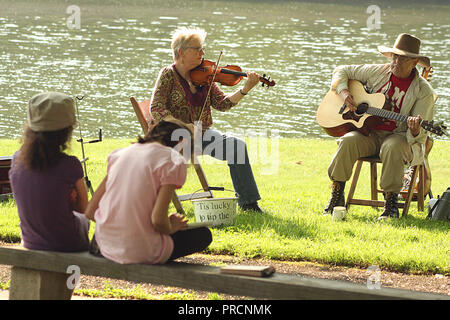 Woman with violin and man with guitar performing outdoors by Abbott Lake on Virginia's Blue Ridge Parkway - Stock Photo