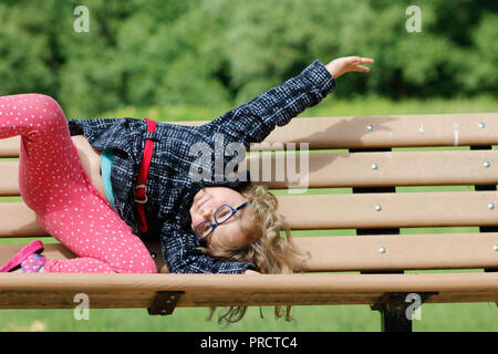 Portrait of cute adorable little red-haired Caucasian girl child making funny silly faces, showing tongue, in autumn fall park outside, playing having fun, lifestyle childhood.. - Stock Photo