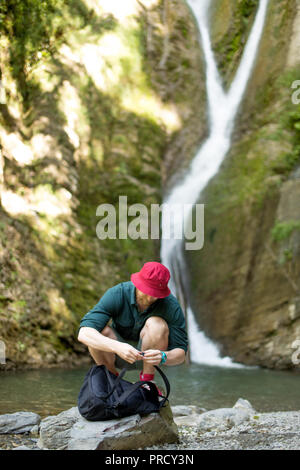 Young tourist camping with backpack near a waterfall in forest. - Stock Photo