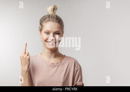 Cheerful young woman finding new idea and raising index finger up. - Stock Photo
