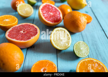 Citrus fruits, whole and sliced on blue wooden background. Selective focus - Stock Photo