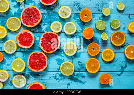 Citrus fruits orange, lemon, grapefruit, mandarin, lime on blue background - Stock Photo