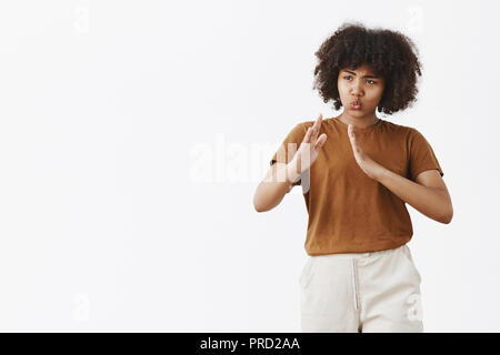 Kiai do not mess with me I know martial arts. Portrait of funny and cute playful African American curly-haired woman in trendy t-shirt raising palms in kung fu pose folding lips over gray wall - Stock Photo