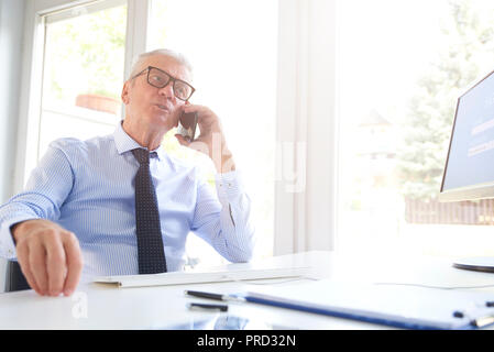 Shot of a senior financial director businessman using cell phone while talking with somebody in the office. - Stock Photo
