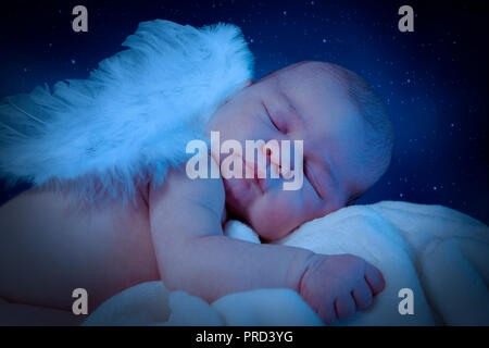 Cute newborn with wings sleeps on cuddly blanket. Night interpreted scene with stars. - Stock Photo