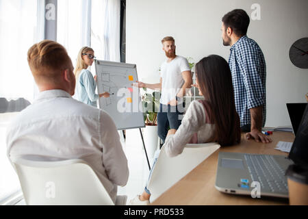 Developing new strategy. Two young colleagues conducting presentation while working with their business team in the office. - Stock Photo