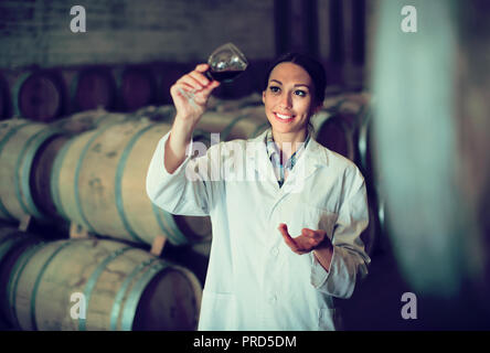 portrait of smiling young woman in white overall looking at wine sample in glass in cellar with woods - Stock Photo