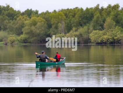BOSSIER PARISH, LA., U.S.A., SEPT. 29, 2018: A man and boy are seen from the rear in a canoe on a beautiful, quiet lake during a fishing trip.
