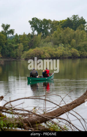 BOSSIER CITY, LA., U.S.A. - Sept. 29, 2018: A man and boy are seen from the rear in a canoe on a beautiful, quiet lake during a fishing trip.