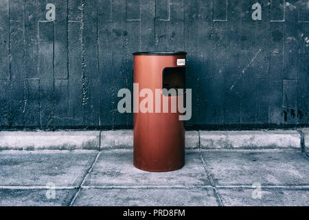 Berlin, Germany, September 30, 2018:  Close-Up of Ashtray on Red Garbage Can Against Gray Wall - Stock Photo