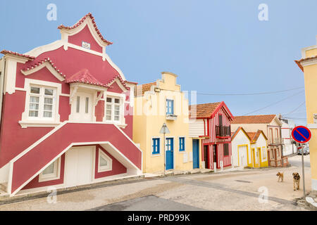 Row of colorful and striped homes on a street, is typical in the coastal town of Costa Nova in Aveiro, Portugal. - Stock Photo