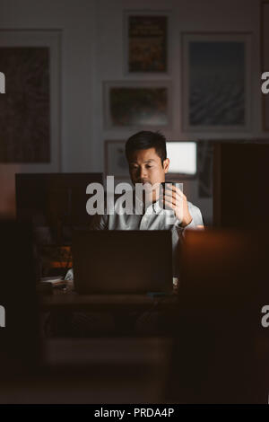 Asian businessman drinking coffee while working in a dark office - Stock Photo