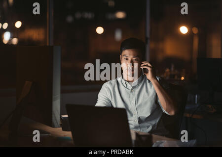 Asian businessman talking on a cellphone in a dark office - Stock Photo