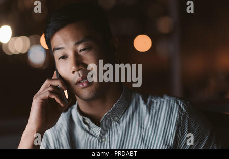 Asian businessman talking on his cellphone in a dark office - Stock Photo