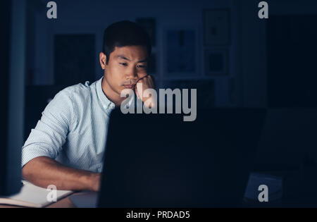 Tired Asian businessman working on a laptop late at night - Stock Photo
