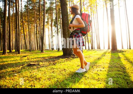 Happy woman hiking in the woods - adventure, travel, tourism, hike and people concept .