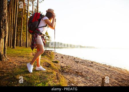 Nature Photographer taking pictures outdoors during hiking trip. - Stock Photo