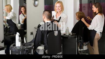 Two female hairdressers working on their clients in a barbershop - Stock Photo