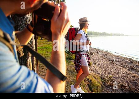 Happy young couples traveler with backpack take photo at forest, Travel and hiking concept. - Stock Photo