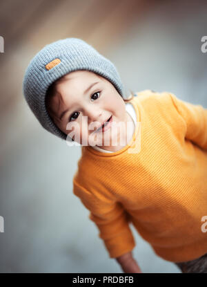 Portrait of a cute happy smiling little baby wearing stylish warm clothes, kids fashion, trendy look in autumn season for boys - Stock Photo