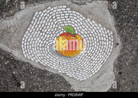 Detroit, Michigan - A pothole patched with an artistic mosaic of a peach on a street in the Eastern Market district. Chicago artist Jim Bachor patched - Stock Photo