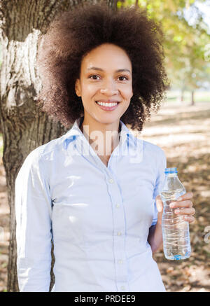 Portrait of smiling young black woman holds bottle of water in nature, afro hair style ,wear blue shirt,  looking at camera - Stock Photo