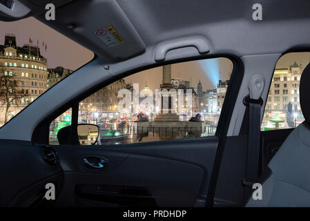 Looking through a car window with view of Trafalgar Square at night with the Big Ben on the background, London, UK - Stock Photo
