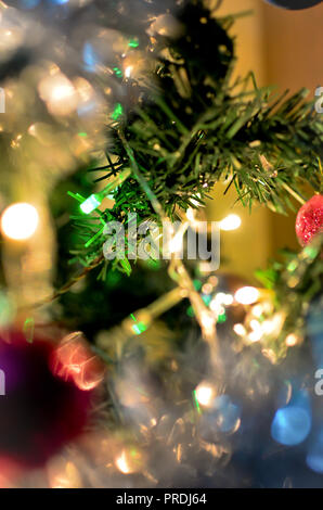 Christmas tree branch with glowing blurred lights in the background - Stock Photo